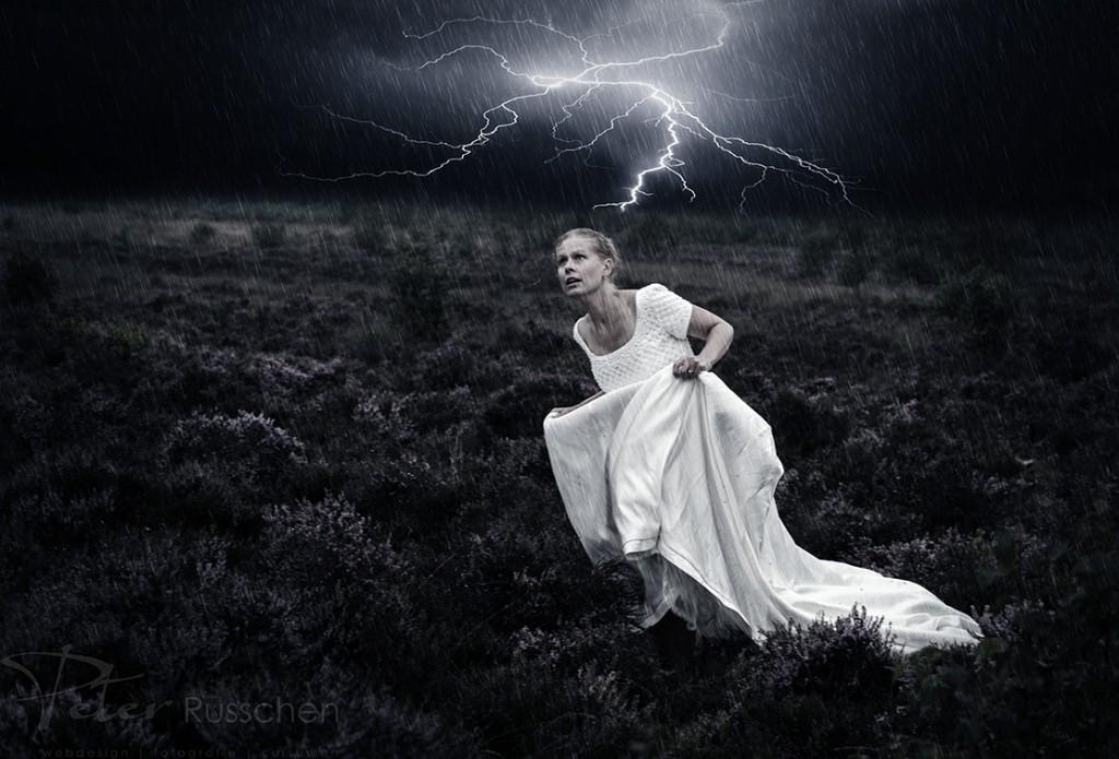 Vrouw rent over de heide in een onweersbui.